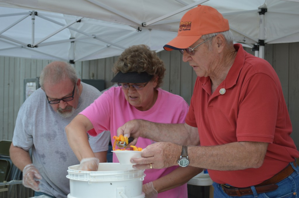 Mayor Pro-tem David Edwards, left, Elaine Korver, and Mayor Roger Granat scoop ice cream to be topped with Palisade Peaches.