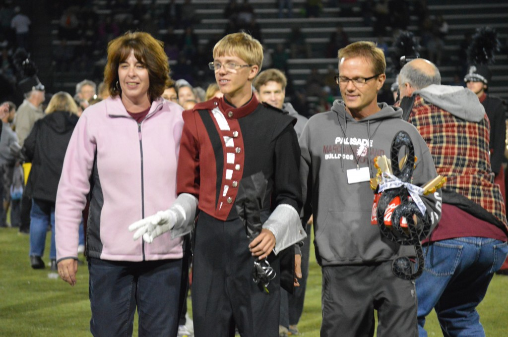 Senior Drum Major Josh Anders is escorted by proud parents Kim and Mike Anders at Friday night's game at Stocker Stadium.